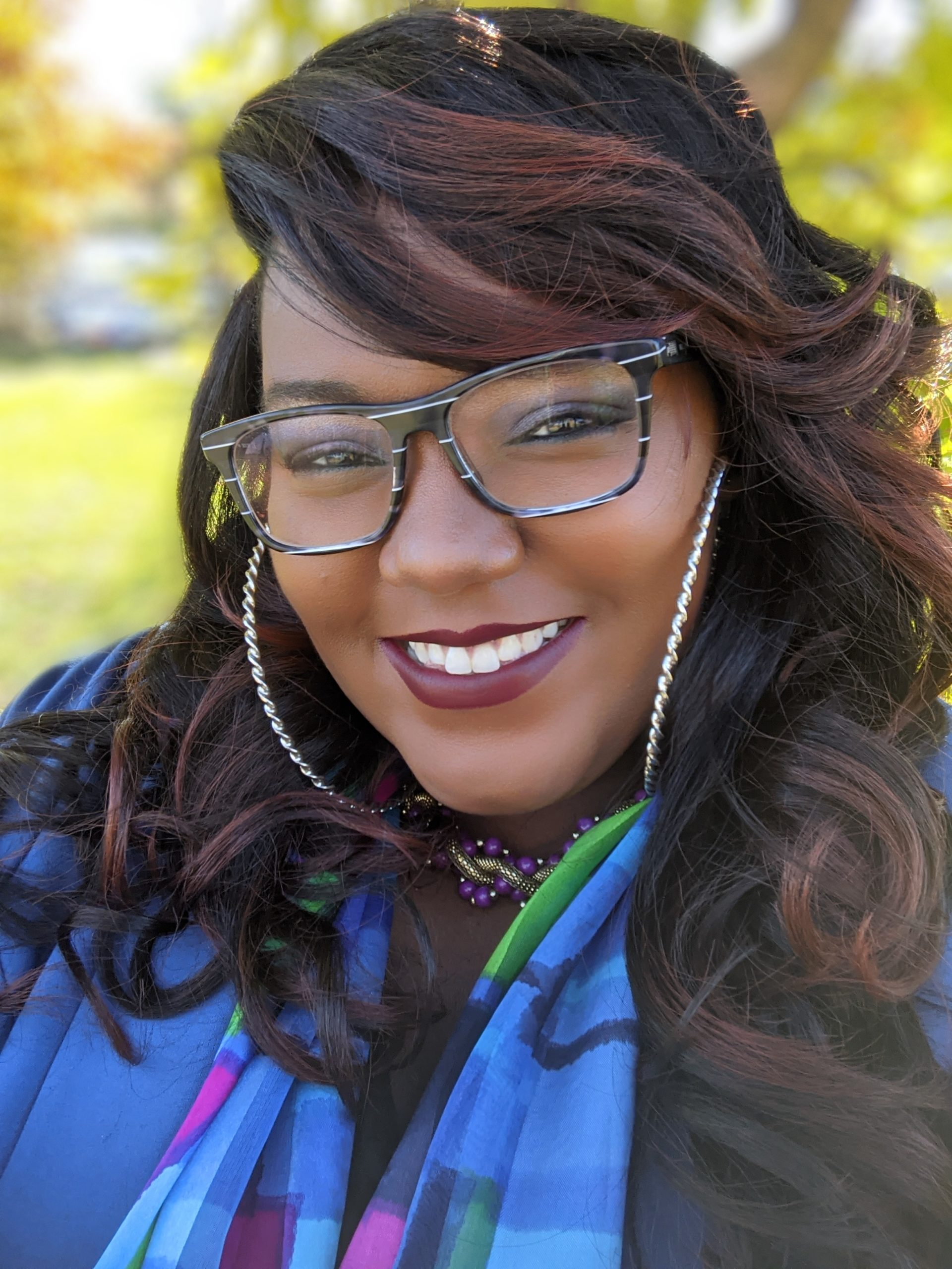 Ariangela Kozik is smiling wide, wearing glasses, big hoops, and a colorful scarf.