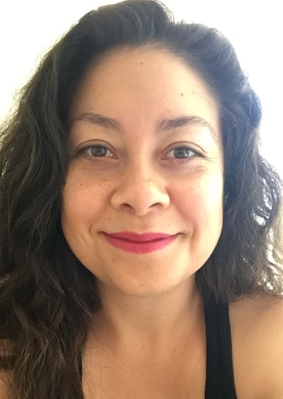 Dr. Monica Gonzalez Ramirez is smiling, wearing pink lipstick, and a black tank top.