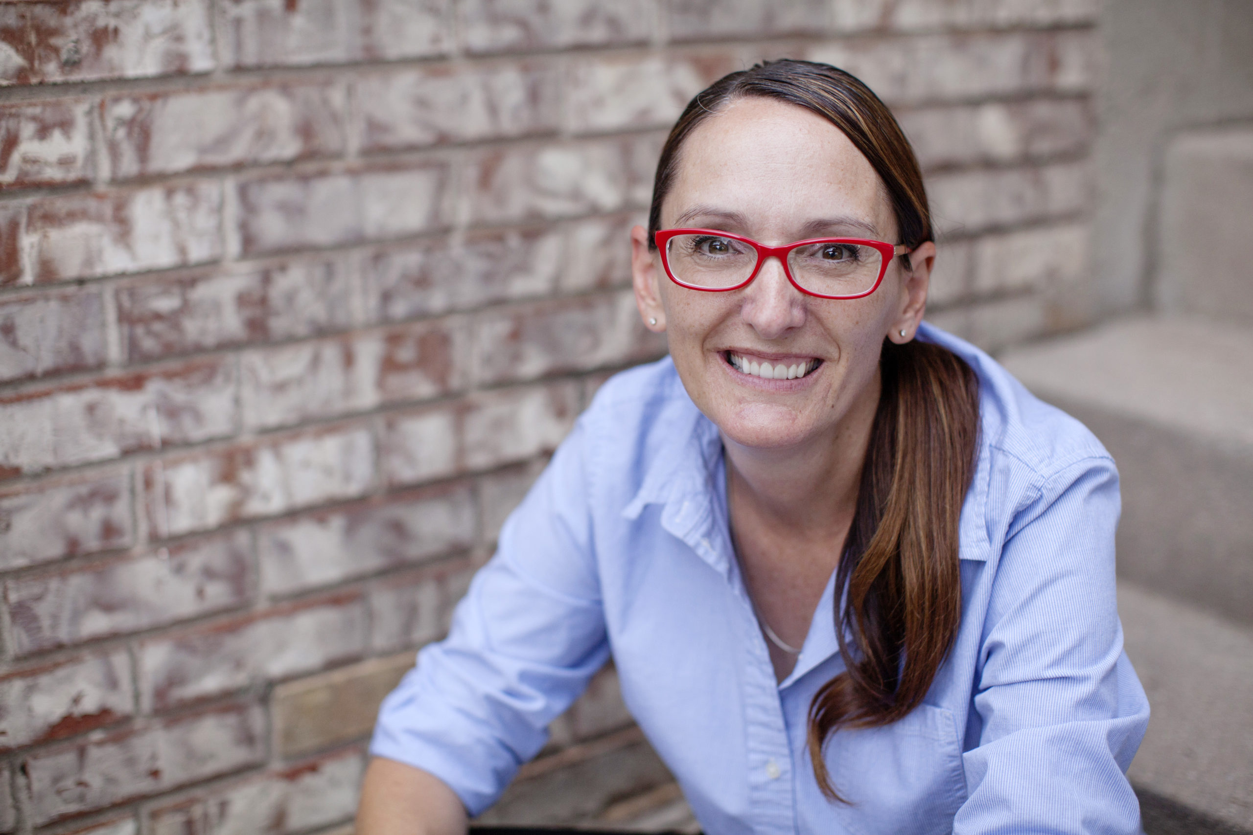 Jessi Smith is smiling wide, wearing bright red glasses and a blue button-down shirt. There's a brick wall behind her.