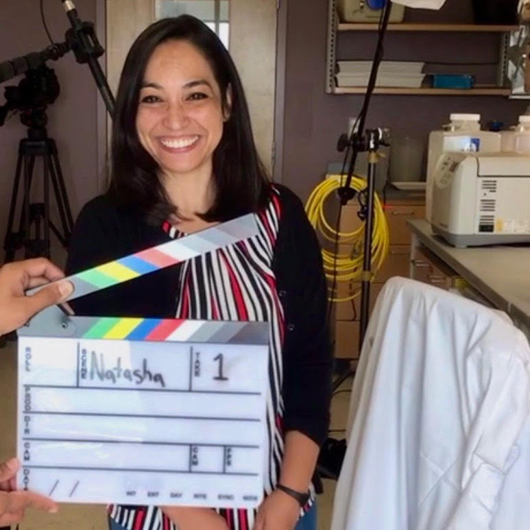 Dr. Tilston is standing in a lab, smiling, and someone is holding a clapperboard with her name on it in front of her.