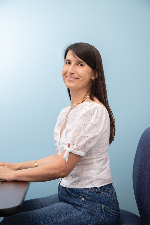 Dr. Fatma Kaplan is typing at a computer and wearing jeans and a white blouse