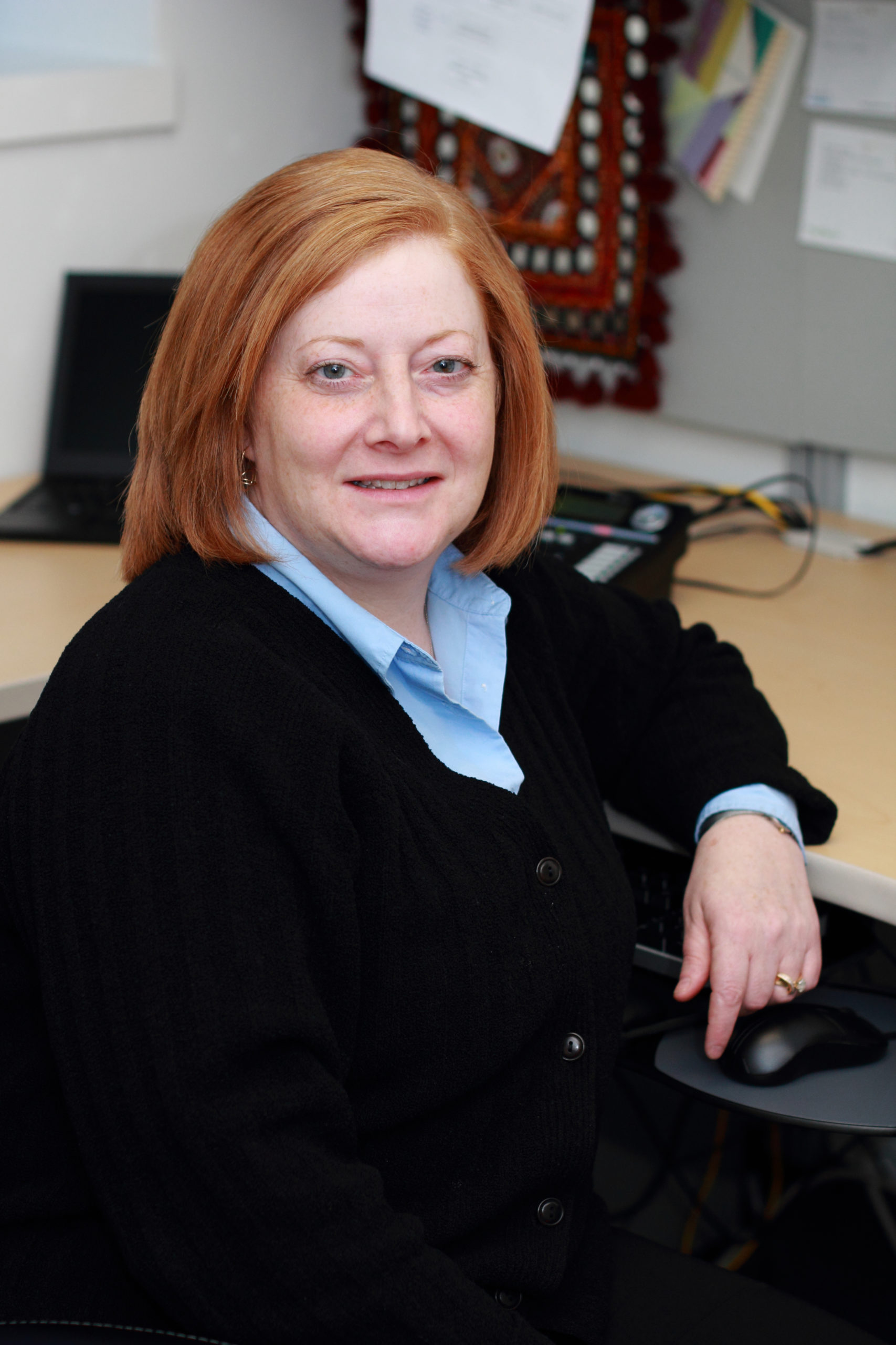 Joanne Kamens has short red hair, is wearing business clothing, and sitting at an office desk.
